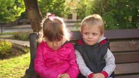 Retrato de duas crianças tristes em um banco de parque vídeos de arquivo