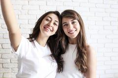 Retrato de duas fêmeas milenares, enganando ao redor na frente da câmera móvel do smartphone Brown eyed as meninas modelo com mor foto de stock