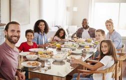 Retrato de duas famílias como apreciam a refeição em casa junto fotografia de stock