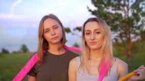 Retrato de duas ginastas das jovens mulheres com equipamento ginástico no monte no por do sol do verão vídeos de arquivo