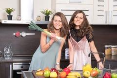 Retrato de duas irmãs gêmeas que têm o divertimento na manhã que prepara o café da manhã Fotografia de Stock