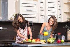 Retrato de duas irmãs gêmeas que têm o divertimento na manhã que prepara o café da manhã Imagem de Stock