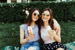 Retrato de duas jovens mulheres que estão junto comendo o gelado que abraça o assento na grama na rua da cidade fotografia de stock royalty free
