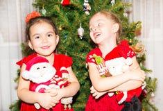 Retrato de duas meninas das crianças em torno de uma árvore de Natal decorada Criança no ano novo do feriado Foto de Stock Royalty Free