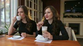 Retrato de duas meninas em um café com um café vídeos de arquivo