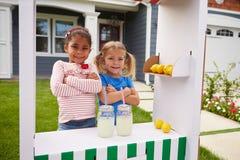 Retrato de duas meninas que correm o suporte de limonada caseiro imagens de stock royalty free