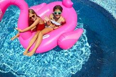 Retrato de duas meninas que vestem os óculos de sol, amigos felizes no flutuador inflável da nadada do flamingo foto de stock royalty free