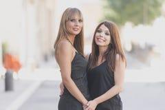 Retrato de duas meninas de sorriso alegres em uma rua da cidade imagens de stock