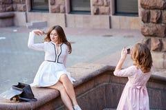 Retrato de duas moças que tomam imagens dse através do telefone celular Foto de Stock