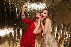 Retrato de duas mulheres alegres entusiasmado em vestidos sparkly Fotos de Stock