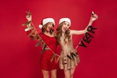 Retrato de duas mulheres atrativas entusiasmado em vestidos sparkly Fotografia de Stock