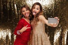 Retrato de duas mulheres bonitas alegres em vestidos sparkly Fotografia de Stock Royalty Free