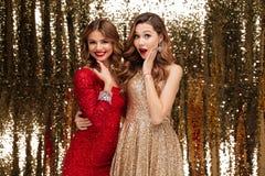 Retrato de duas mulheres entusiasmado de sorriso em vestidos sparkly Fotografia de Stock Royalty Free
