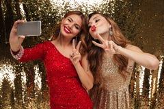 Retrato de duas mulheres felizes engraçadas em vestidos sparkly Foto de Stock Royalty Free