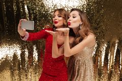 Retrato de duas mulheres de sorriso bonitas em vestidos sparkly Imagens de Stock Royalty Free