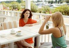 Retrato de duas namoradas consideravelmente modernas em beber interior do ar livre do café e na falar, tendo o bate-papo e o coct imagem de stock royalty free