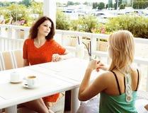Retrato de duas namoradas consideravelmente modernas no inte do ar livre do café fotos de stock