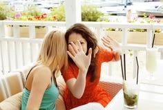 Retrato de duas namoradas consideravelmente modernas no inte do ar livre do café imagem de stock