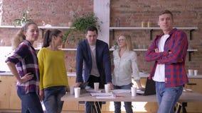 Retrato de empresários bem sucedidos no escritório moderno, de homens criativos da equipe e de comunicação das mulheres no trabal