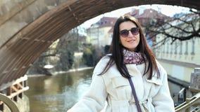 Retrato de encantar al turista femenino hermoso que presenta en el terraplén de la ciudad en el puente que mira la cámara almacen de video