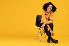 Retrato de encantar a jovem mulher afro-americano com sorriso bonito vestida na roupa ocasional que senta-se no à moda fotografia de stock royalty free