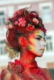 Retrato de estátua viva de um multicolorido da mulher vestida Foto de Stock