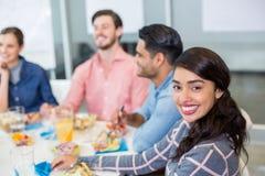 Retrato de executivo fêmea feliz comendo o café da manhã Fotos de Stock Royalty Free