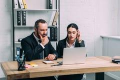 retrato de executivos focalizados nos ternos usando o portátil junto no local de trabalho imagem de stock royalty free
