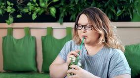 Retrato de fazer dieta o cocktail saudável bebendo do verão da mulher gorda feliz com as ervas que olham a câmera filme