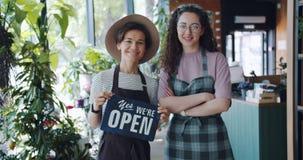Retrato de floristas bonitos en tienda de flor con la muestra abierta que comienza negocio almacen de metraje de vídeo