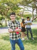 Retrato de fones de ouvido vestindo e da escuta do adolescente a música com amigos foto de stock royalty free