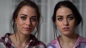 Retrato de gêmeos novos bonitos das irmãs com caras sérias, um de que cobre o lado direito da cara com a palma video estoque
