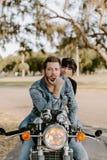 Retrato de Guy Girl Couple Riding de moda de moda moderno joven apuesto atractivo en escuela vieja del crucero verde de la motoci fotografía de archivo