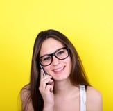Retrato de hablar femenino joven en el teléfono con sonrisa en aga de la cara Foto de archivo libre de regalías