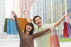 Retrato de hacer compras que va joven, sonriente de los pares y de sostener bolsos de compras coloridos en la calle, al aire libre Foto de archivo libre de regalías