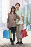 Retrato de hacer compras que va joven, sonriente de los pares y de sostener bolsos de compras coloridos en la calle, mirando la cá Imagenes de archivo