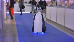 Retrato de hacer publicidad el robot que se mueve a lo largo de la alfombra azul en la exposición robototechnic metrajes