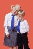 Retrato de hermanos jovenes en uniforme escolar con el brazo alrededor sobre fondo anaranjado fotografía de archivo libre de regalías