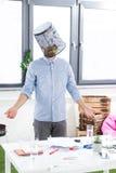 Retrato de homem de negócios confuso com a cubeta do lixo na cabeça no escritório fotografia de stock