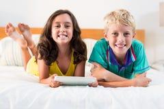 Retrato de irmãos de sorriso com a tabuleta digital que encontra-se na cama Fotos de Stock Royalty Free
