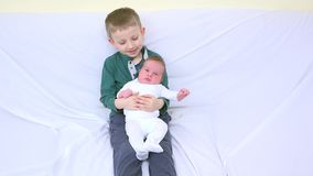 Retrato de irmãos felizes, a criança a mais grande que guarda recém-nascida em seu braço, sorrindo video estoque