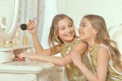 Retrato de irmãs bonitos nos vestidos dourados que sentam-se perto da tabela de pingamento imagem de stock