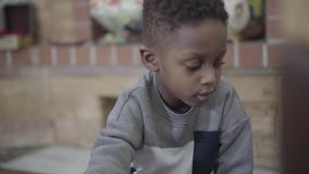 Retrato de jogar focalizado da criança menino afro-americano pequeno e de ter o divertimento com os brinquedos na sala de visitas video estoque