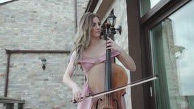 Retrato de jogos bem sucedidos do violoncelista no violoncelo no balcão video estoque