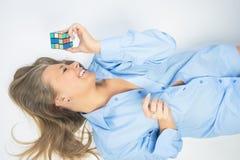 Retrato de jugar femenino rubio sonriente feliz con el cubo de Rubik Foto de archivo libre de regalías