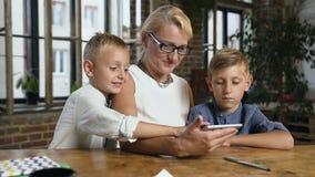 Retrato de la abuela preciosa con sus nietos que usan la tableta para el vídeo que charla mientras que se sienta en el escritorio almacen de video