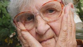 Retrato de la abuela triste con emociones y sensaciones Mujer mayor que mira la cámara con la expresión triste al aire libre almacen de metraje de vídeo