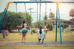 Retrato de la acción de los niños que se divierten que balancea en el parque Fotos de archivo libres de regalías
