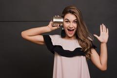 Retrato de la audiencia de la mujer joven a través de una lata con una palma abierta sobre gris foto de archivo libre de regalías