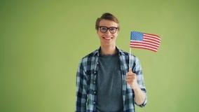 Retrato de la bandera americana de la tenencia del patriota de los E.E.U.U. que sonr?en mirando la c?mara almacen de video